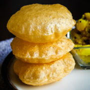 stack of 3 pooris in a plate with batata bhaji in the back.