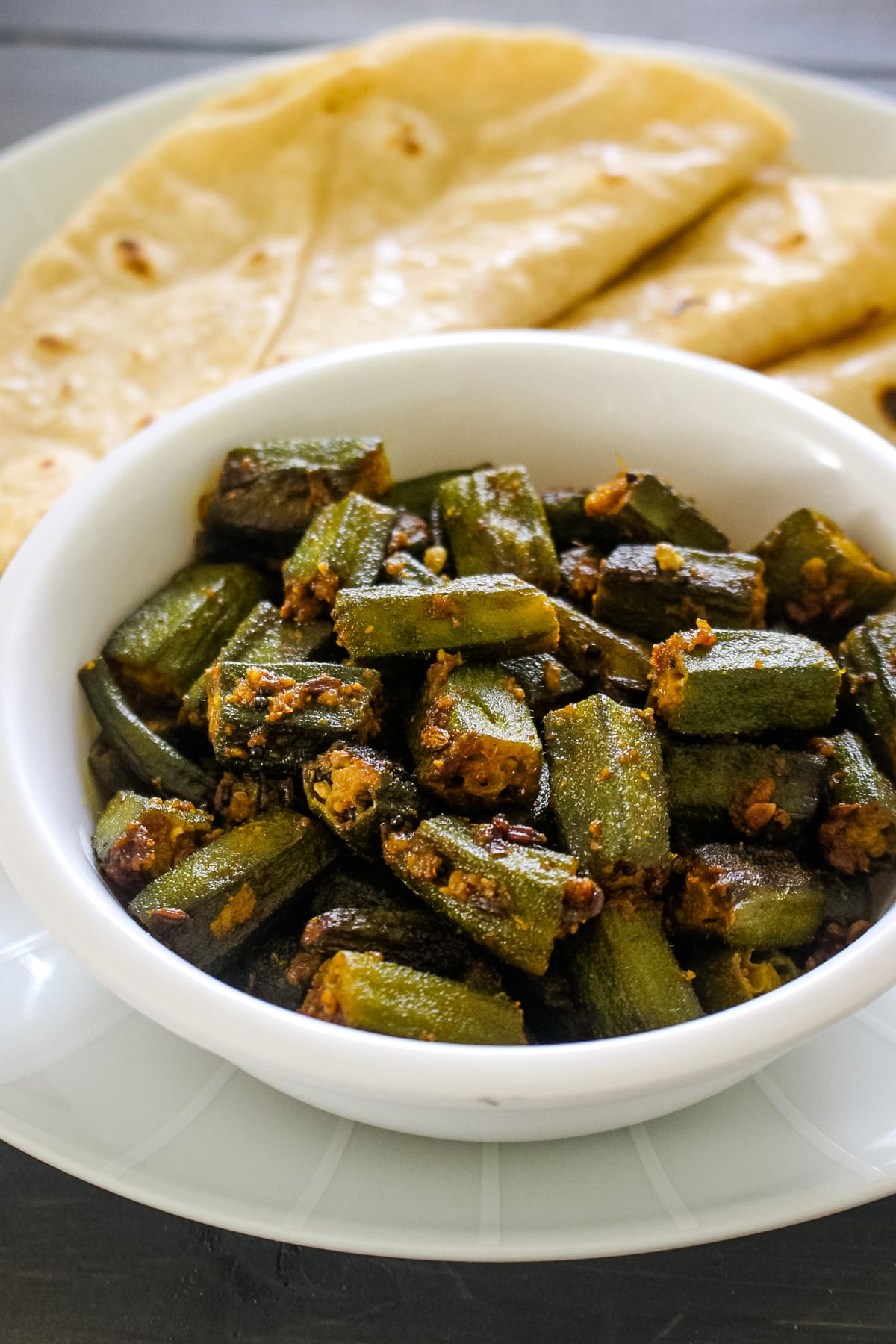 Close up of achari bhindi served with roti.