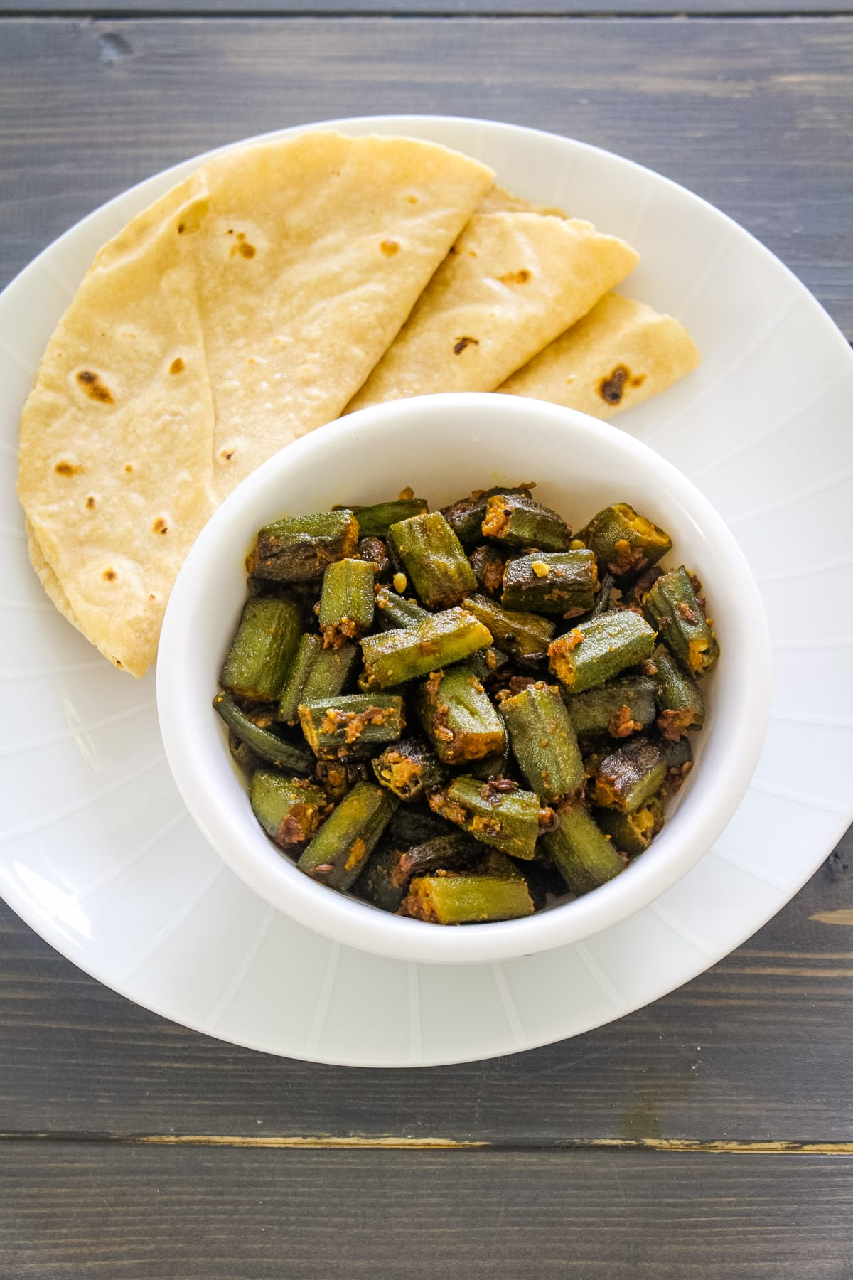 Achari bhindi served with a bowl with 3 phulka roti.