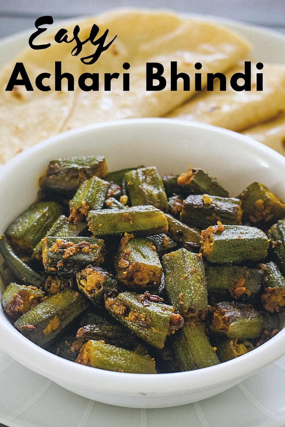 Achari bhindi served with 3 roti with text on the image.