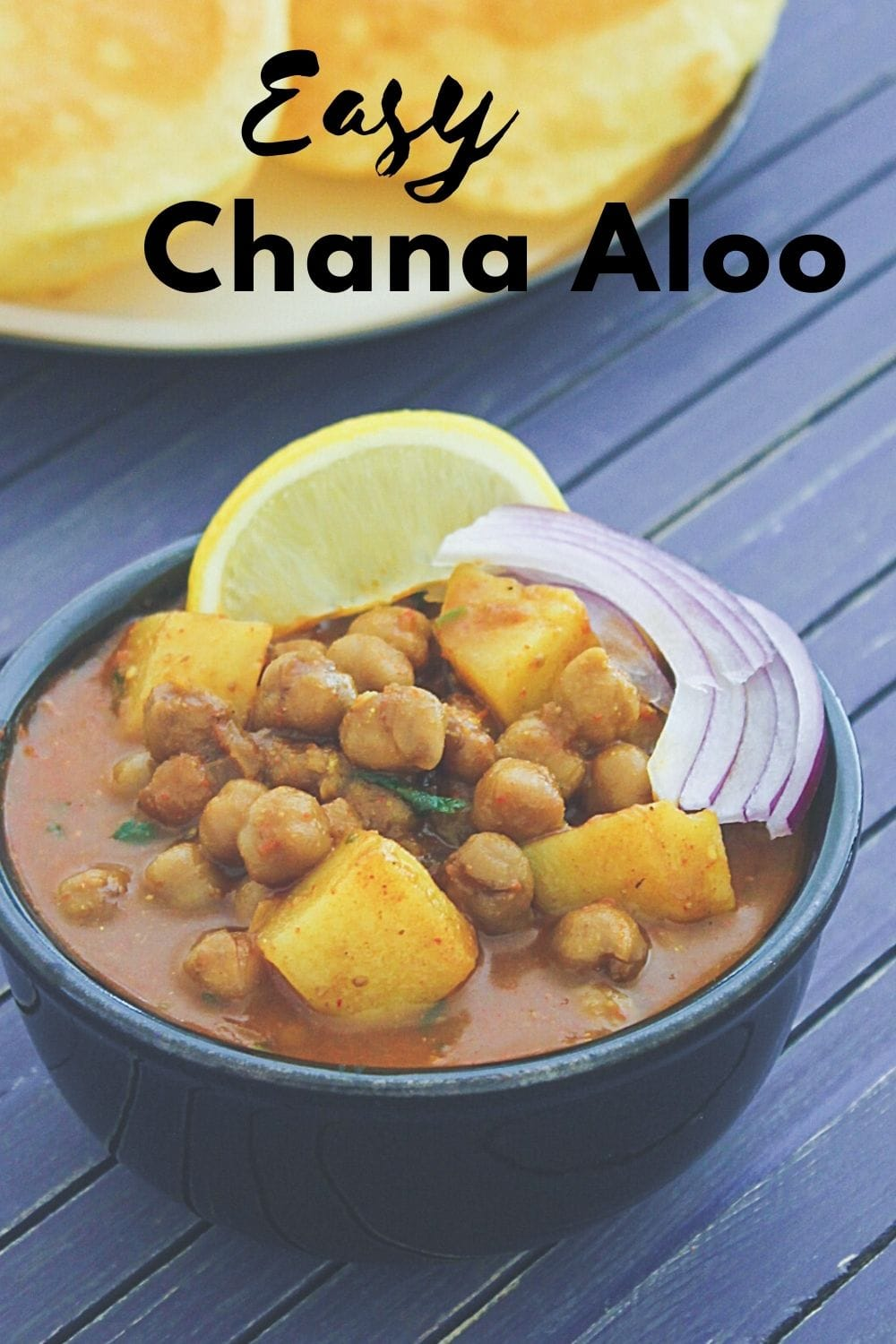 Aloo chana served in a bowl with sliced onion and lemon wedge with text on the image.