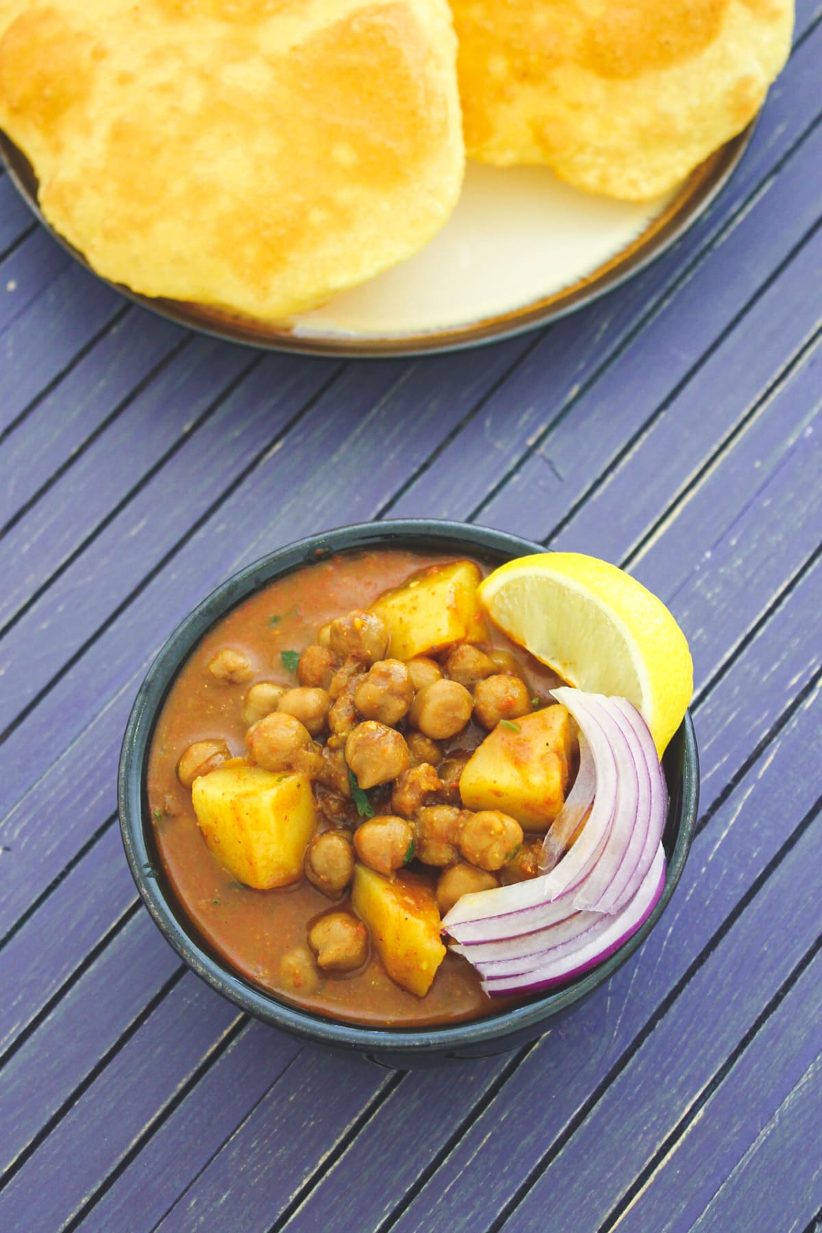Aloo chole served in a bowl with garnish of onions and lemon wedge, bhatura on the side.