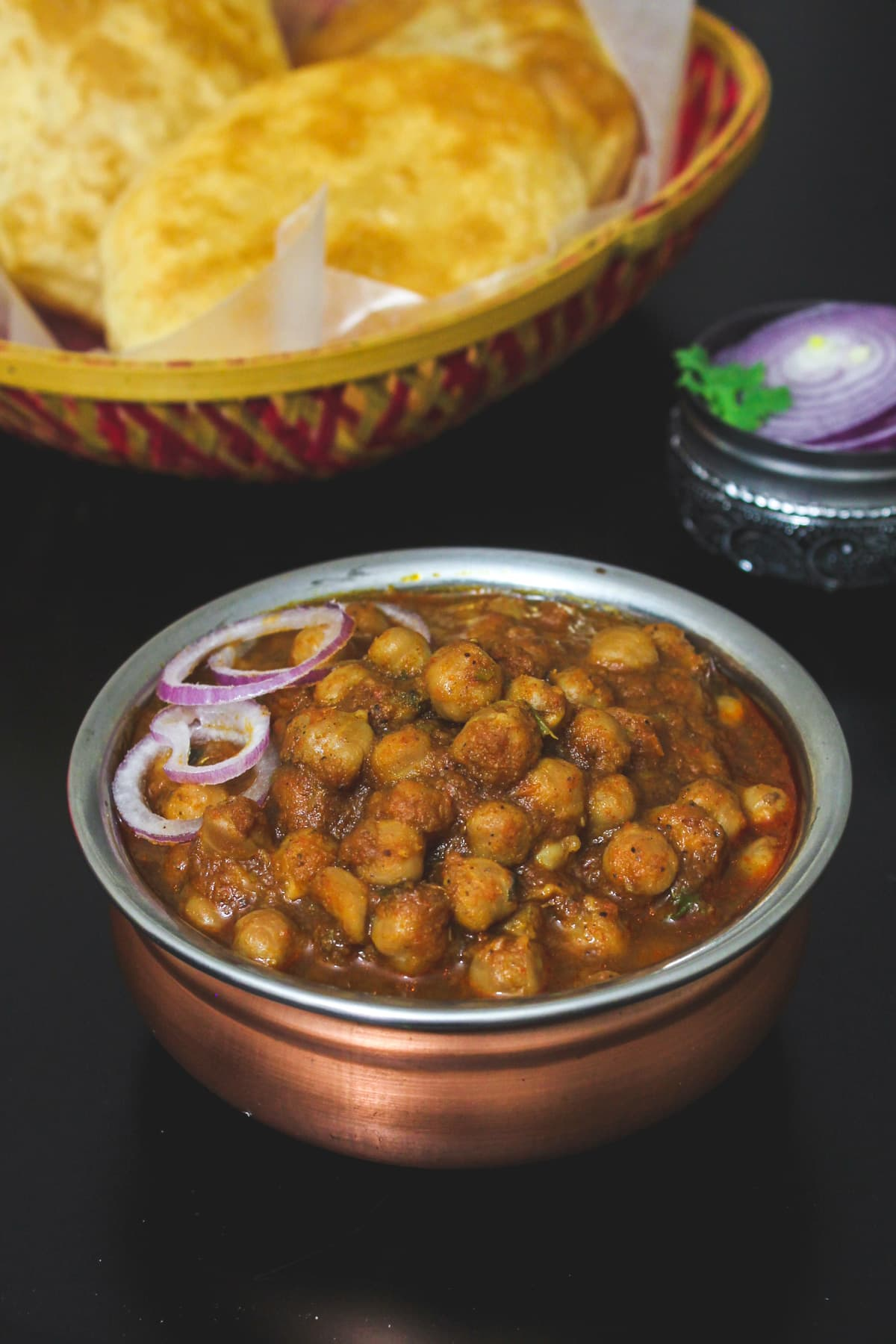 Close up of chole masala garnished with onion rings.