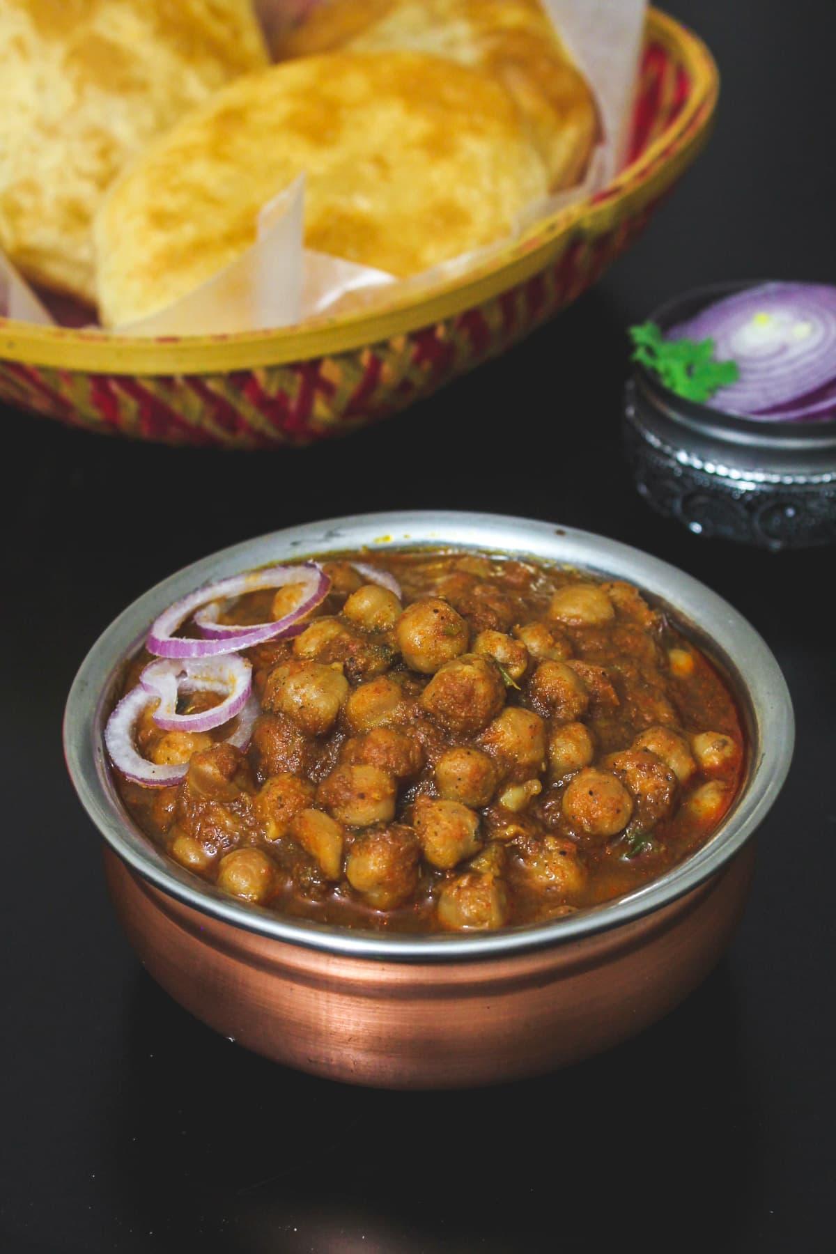 Close up of chole masala garnished with onion rings.