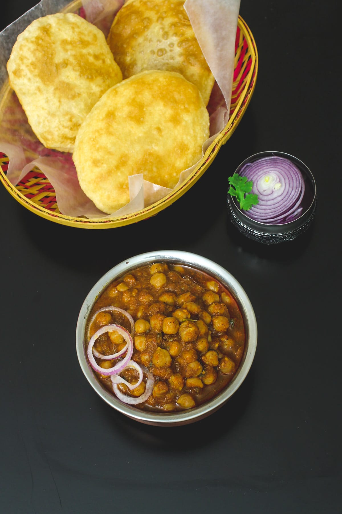 Punjabi chole served with onion and bhatura.