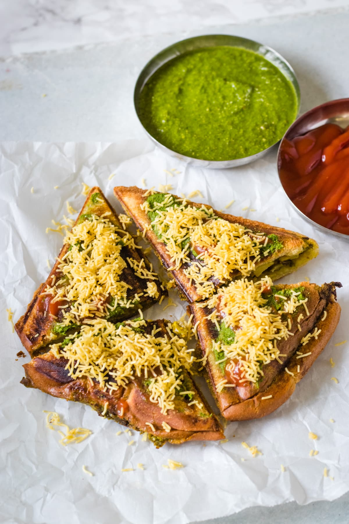Masala toast sandwich garnished with sev and served with green chutney, ketchup.