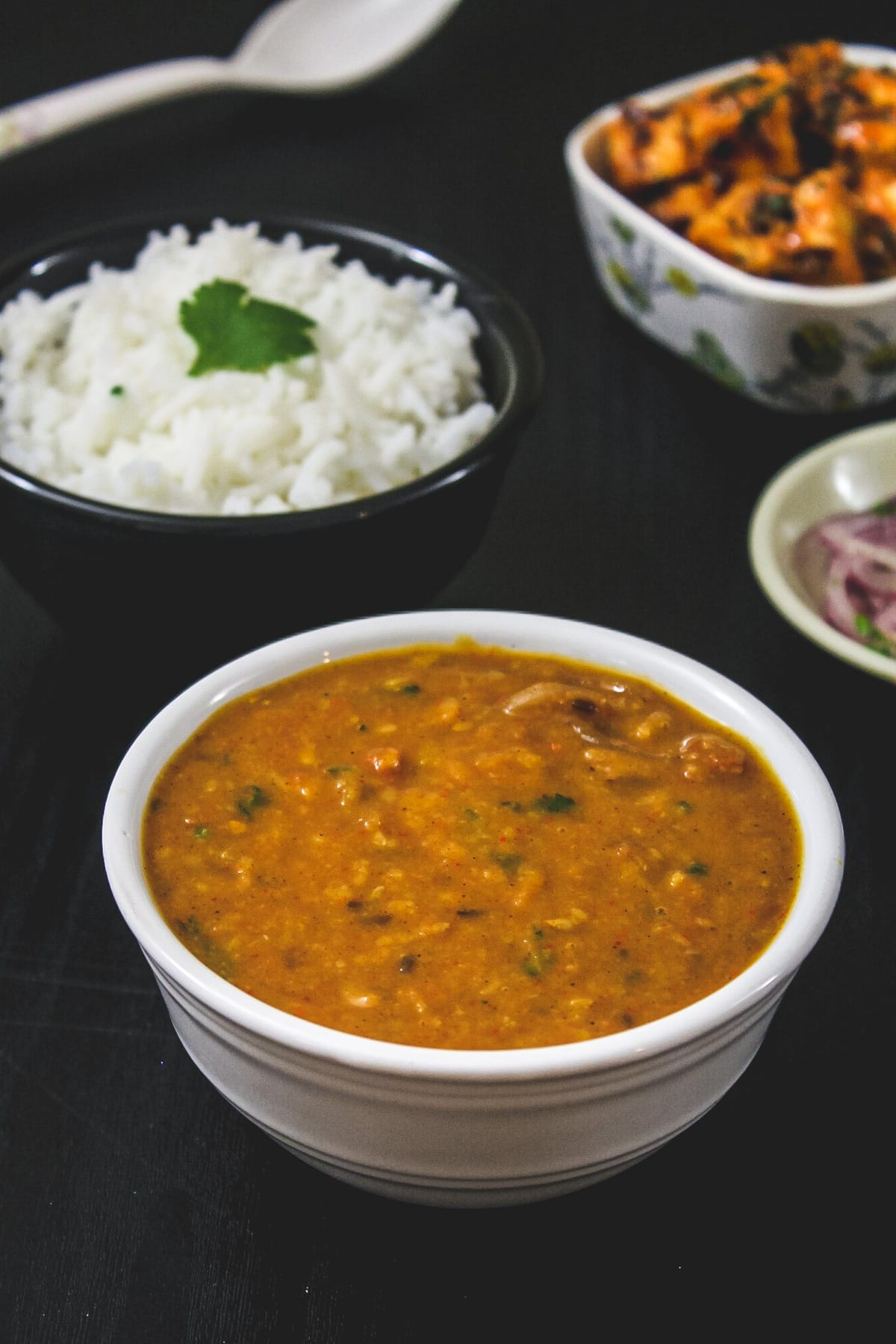 Toor dal in a bowl with side of rice and paneer sabzi.
