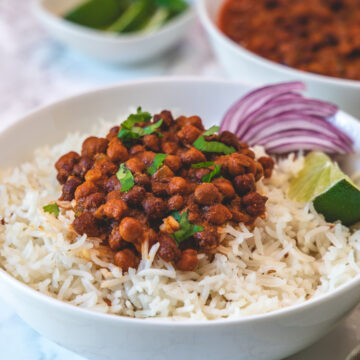 Kala chana masala served over a bowl of rice with side of sliced onions and lime wedge.