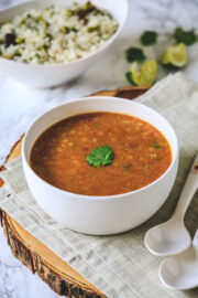 toor dal in a bowl with cilantro served with pulao.