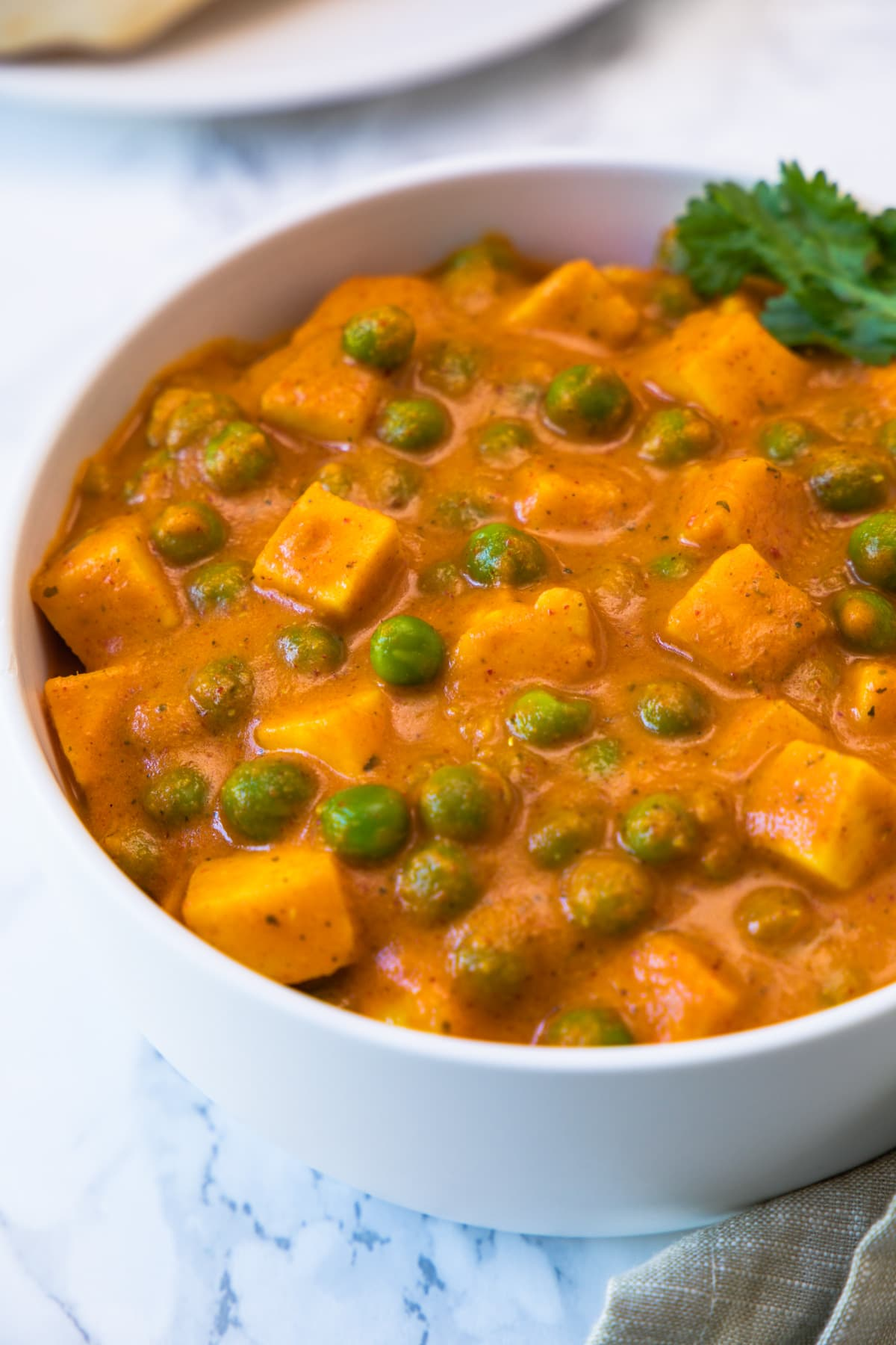 Close up of matar paneer curry in a white bowl