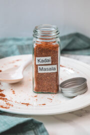 Kadai masala powder in a glass spice jar in a plate with spoon and lid with napkin on side.