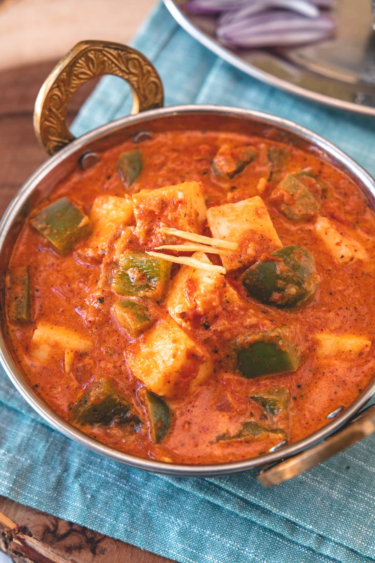 Close up of kadai paneer in a serving wok with napkin underneath.