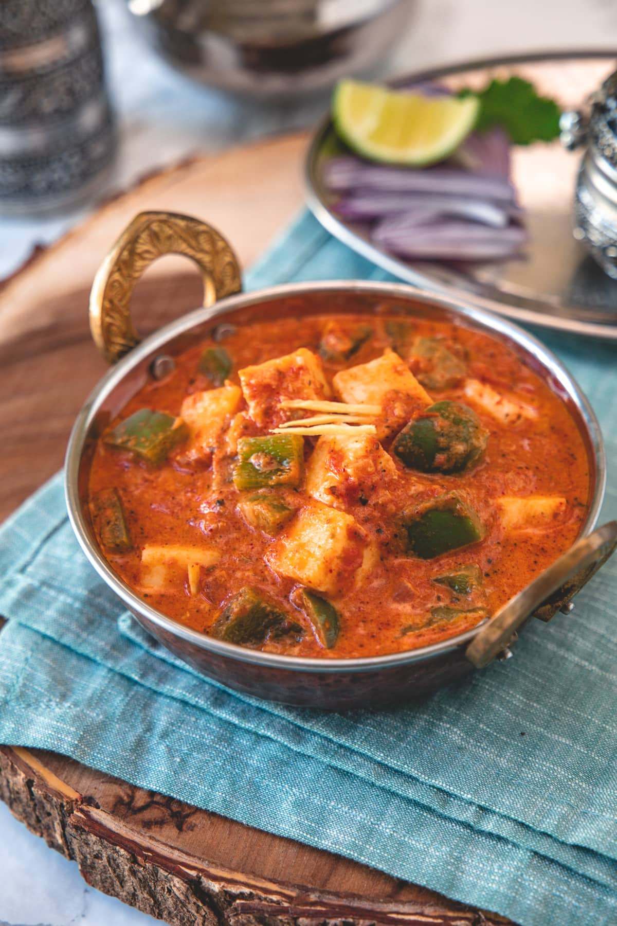 Kadai paneer served in a serving wok with onions, lime on side with napkin underneath.