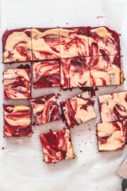 Top view of red velvet cheesecake swirl brownie pieces on a parchment paper with knife on the side.
