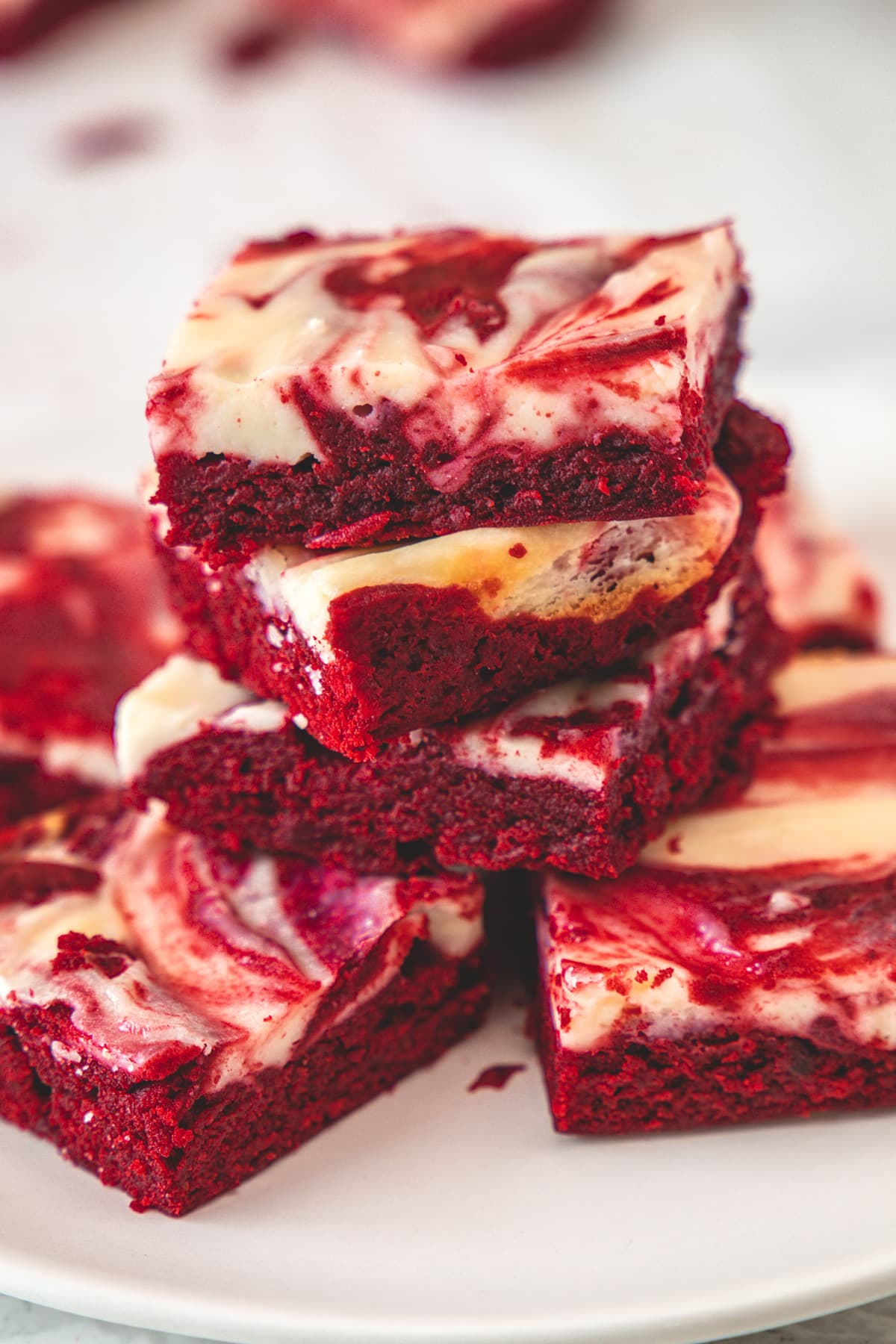 Stack of red velvet cheesecake brownies in a white plate.