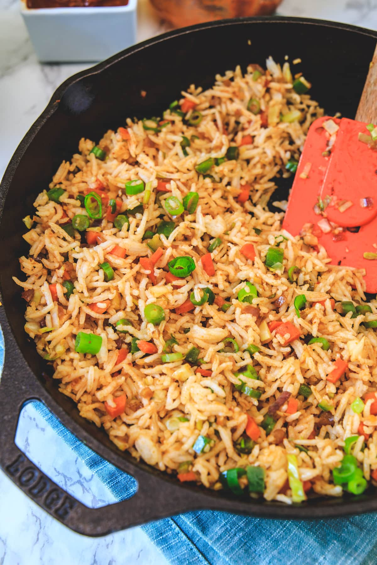 schezwan fried rice in a cast iron pan with spatula.