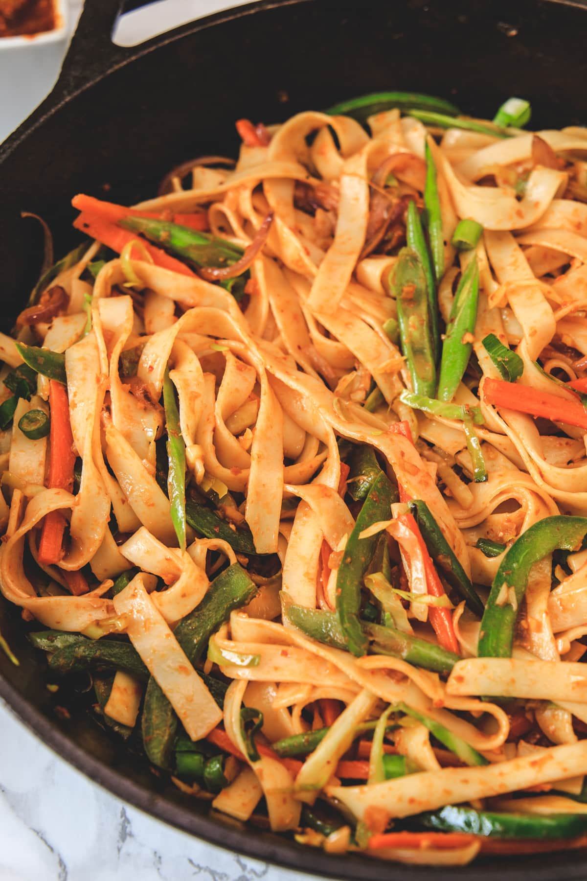 Close up of schezwan noodles in the cast iron pan.