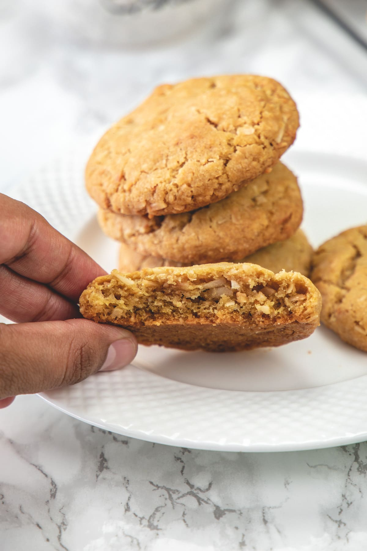 halved eggless coconut cookie to show inside texture with a stack of cookies behind.