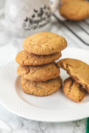 Stack of 4 eggless coconut cookies in a plate with one cookie broken into half on the side.