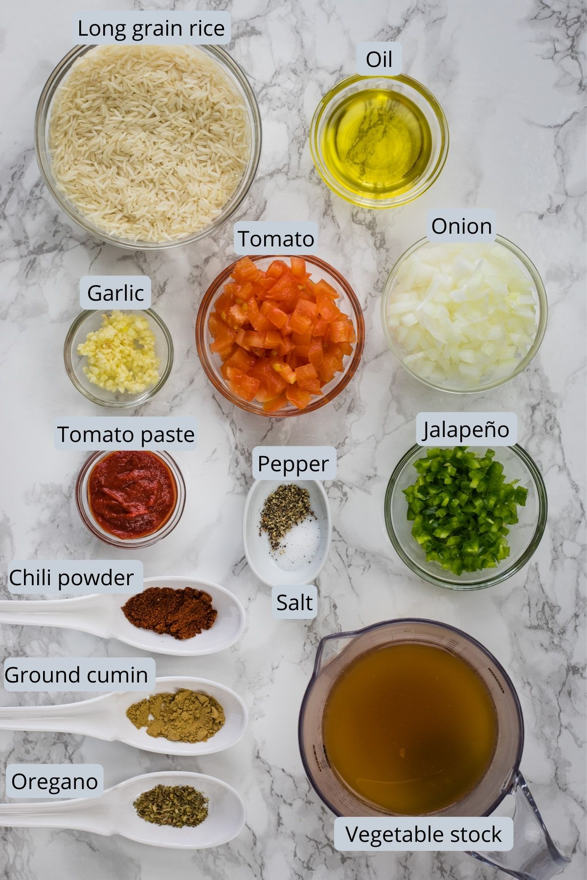 Ingredients used in Mexican rice in individual bowls and spoons on marble surface.