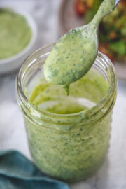 A spoonful of avocado lime dressing drizzling back into the mason jar to show consistency.