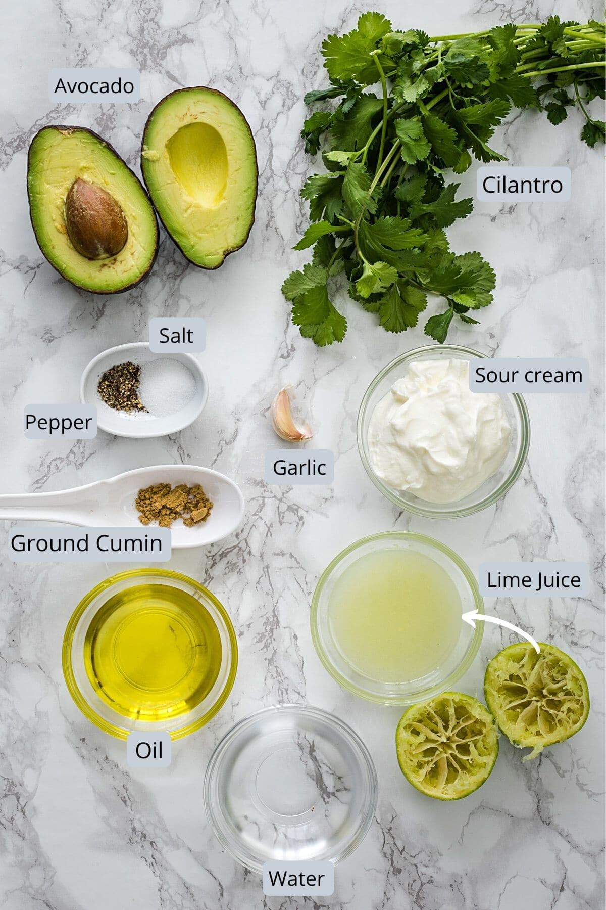 Ingredients used in avocado lime dressing in individual bowls on marble surface.