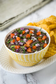 Black bean dip in a bowl garnished with onion, tomato, cilantro and served with tortilla chips.