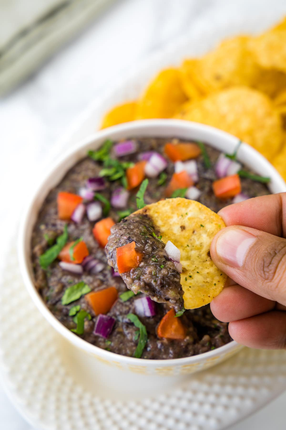 A scoop of black bean dip with tortilla chip.