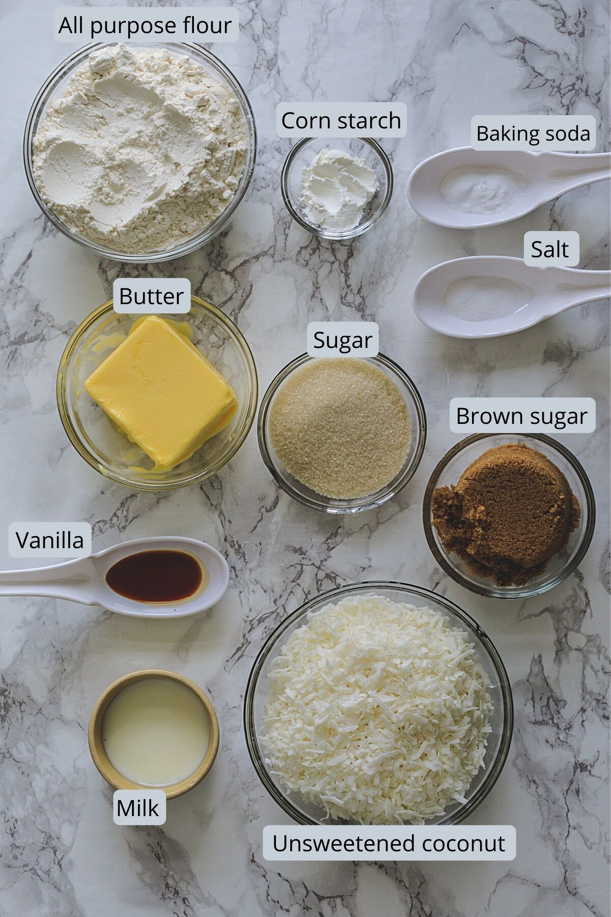Ingredients used in eggless coconut cookies removed in individual bowls on marble surface.