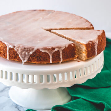 Eggless lemon cake with one slice cut on the cake stand with green napkin on side.