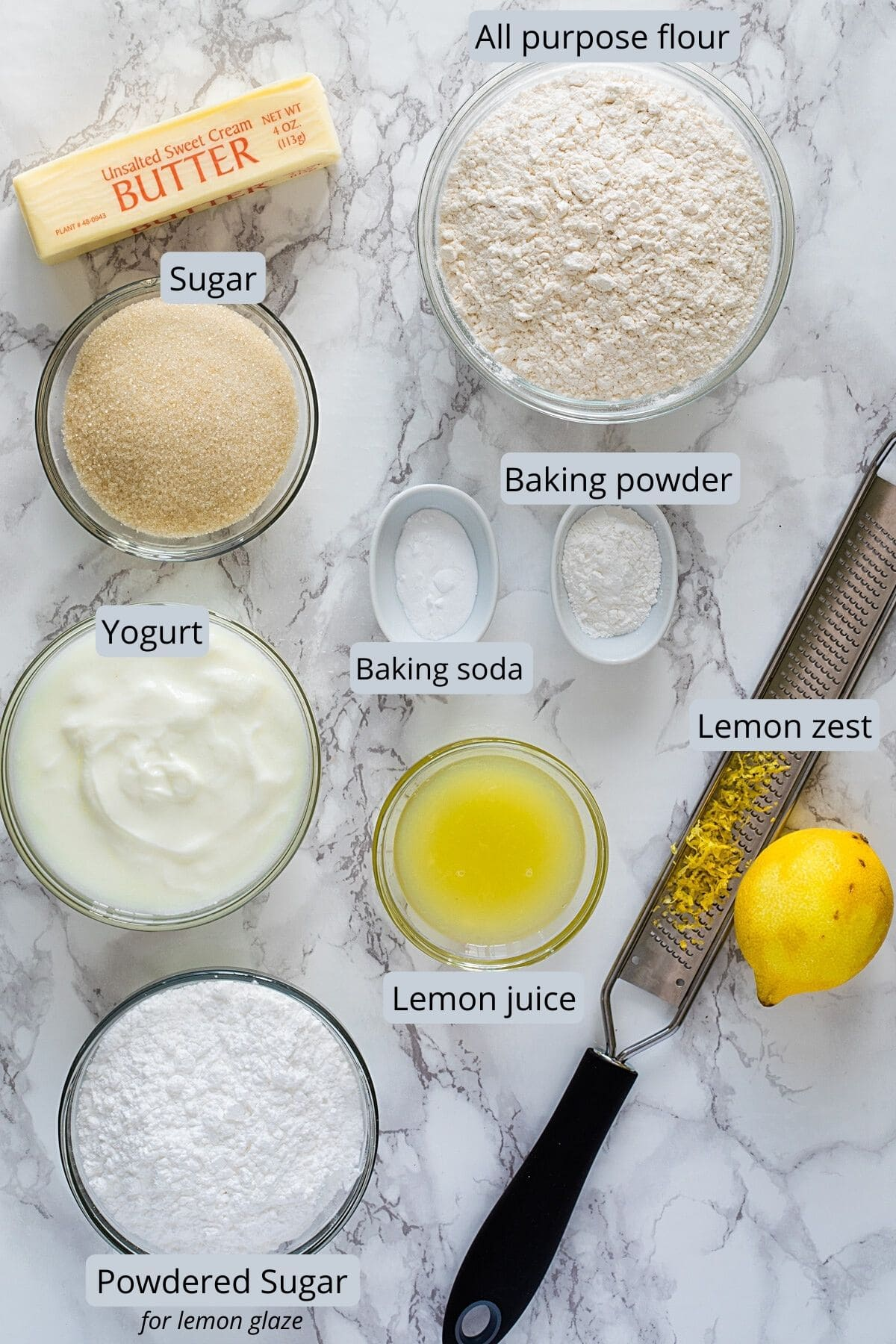 Ingredients used in eggless lemon cake in individual bowls on a marble surface.