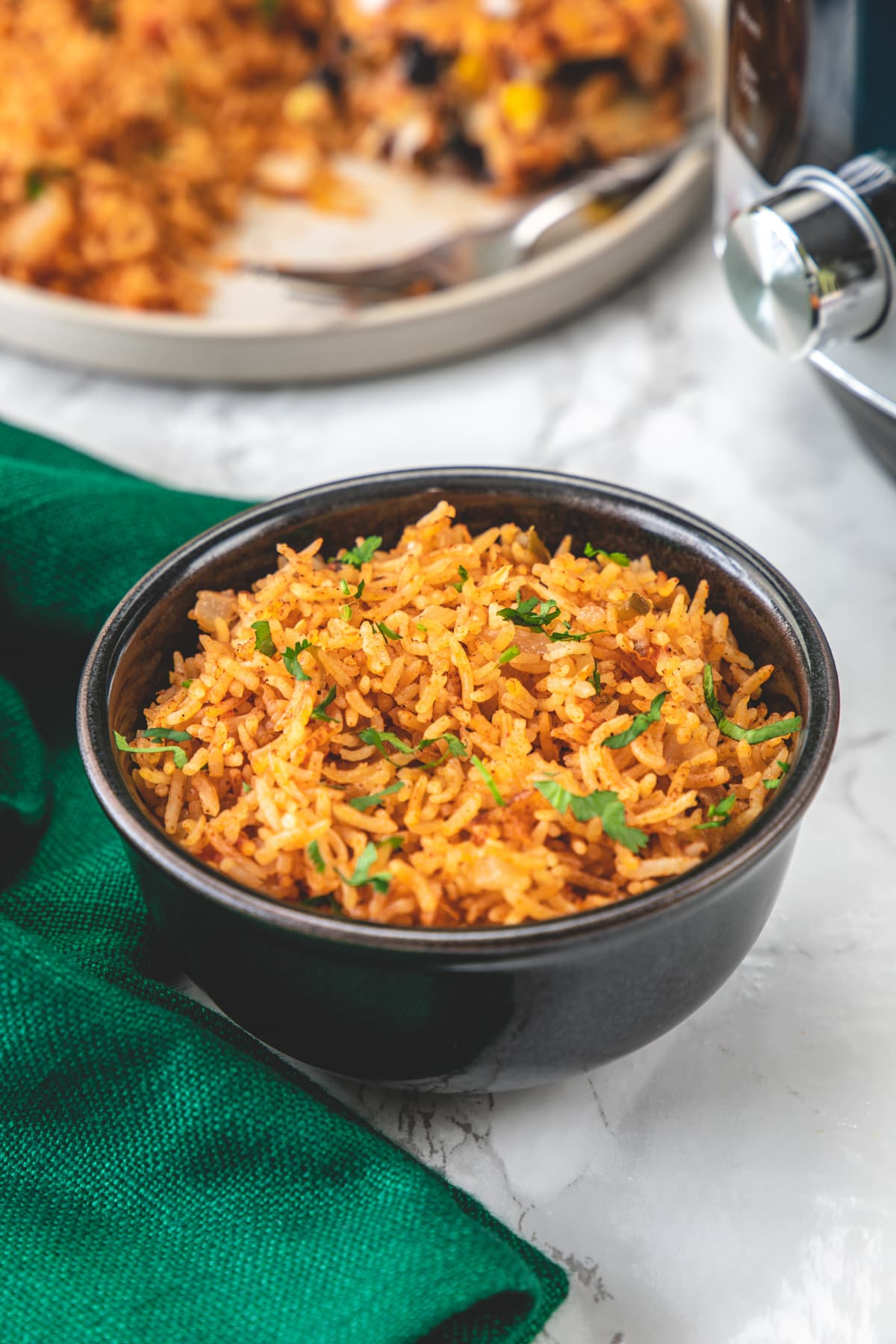 Mexican rice in a black bowl with green napkin on left and instant pot on right side.