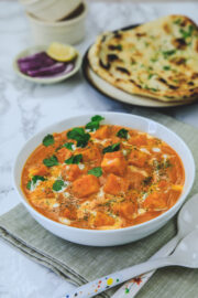 Paneer butter masala garnished with cream and cilantro on the napkin served with naan and onions.