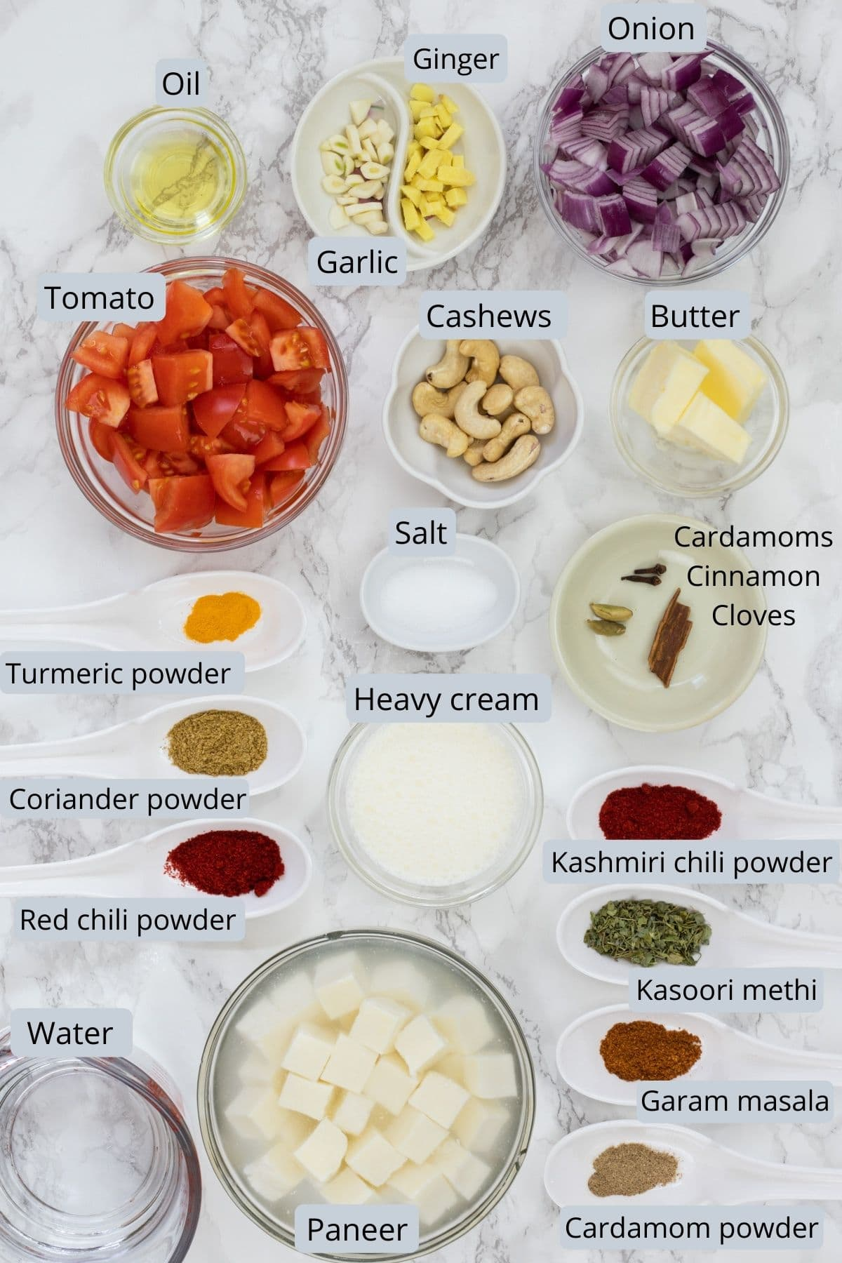 Paneer butter masala recipe ingredients in individual bowls and spoons on marble surface.