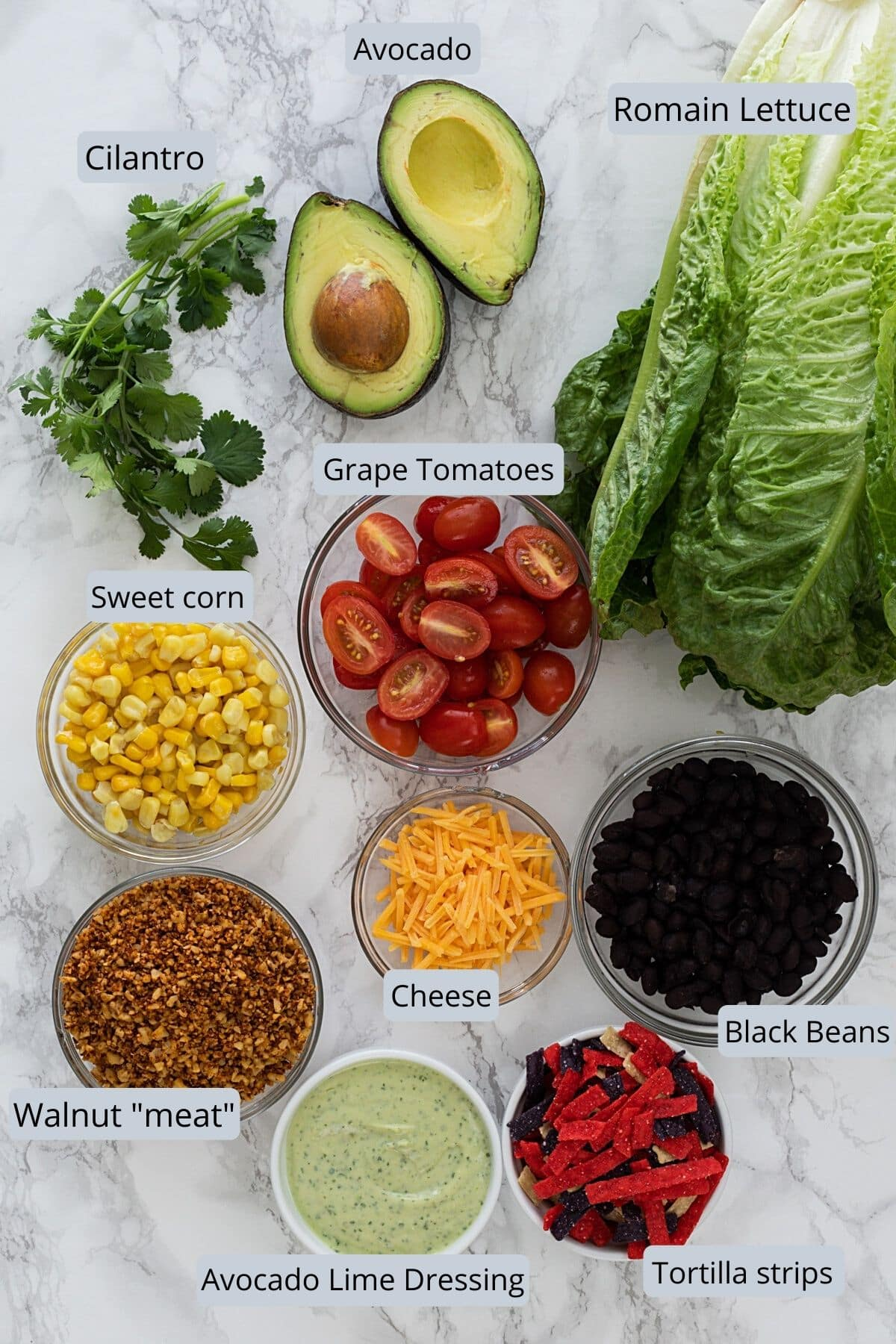 Ingredients used in vegetarian taco salad in individual bowls on marble surface.
