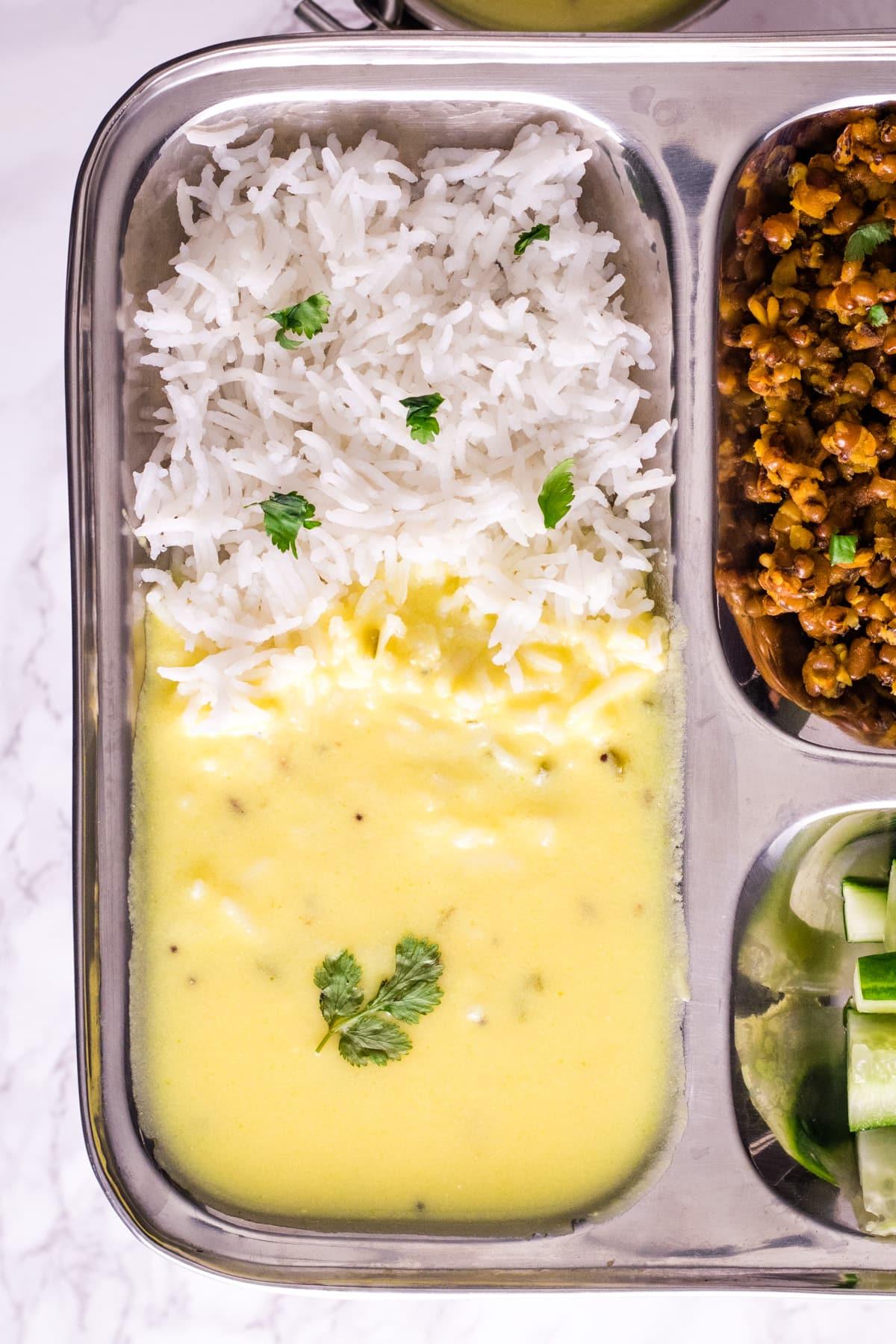 Gujarati kadhi served with rice in a steel plate.