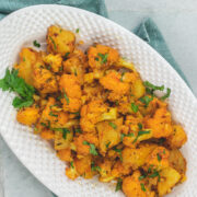 Aloo gobi masala served in an oval platter and garnished with cilantro.