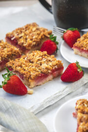 Strawberry cake squares on marble with few strawberries place around.