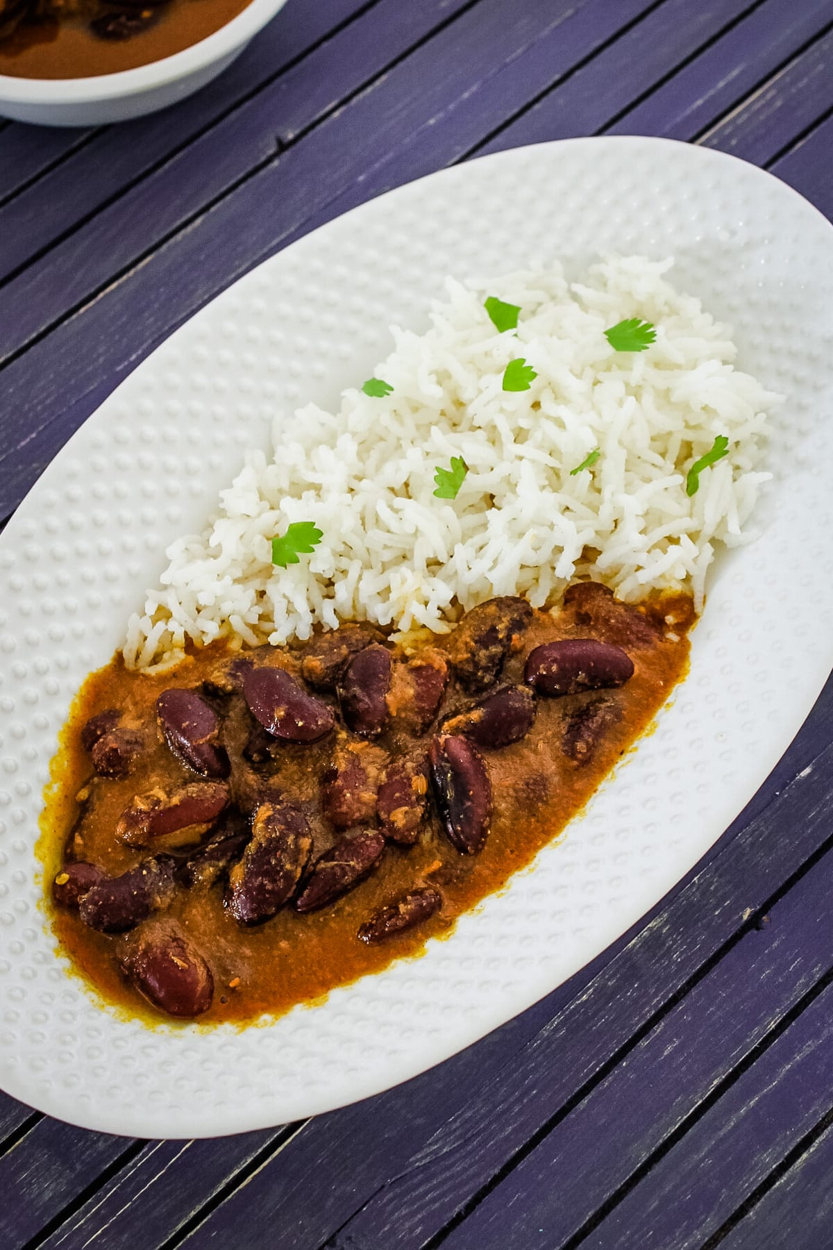 Rajma chawal served in oval plate, garnished with cilantro.