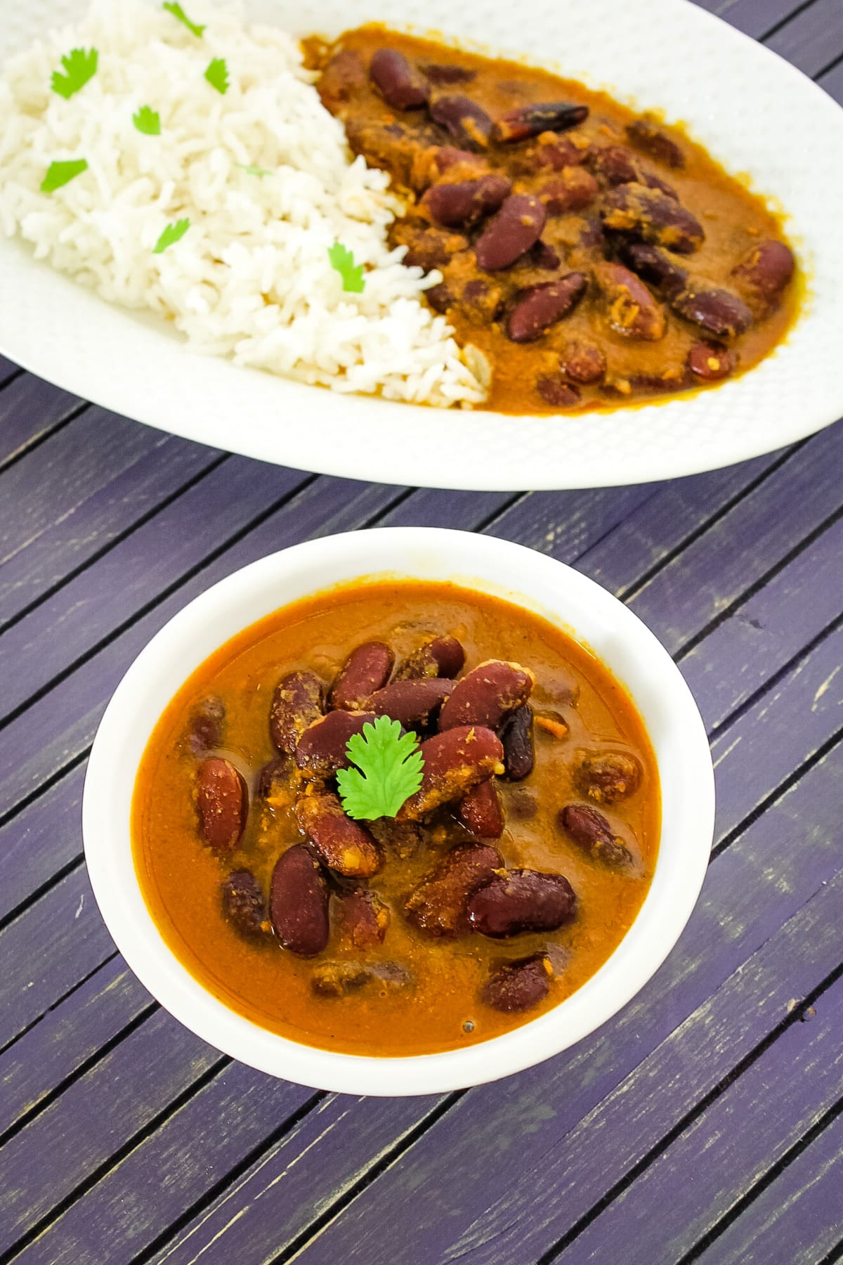 Rajma curry in a bowl and rajma chawal in a plate in back.