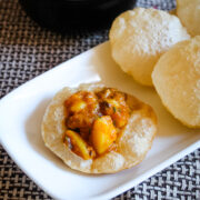 Aloo curry served on puri with few more puri and curry on side.