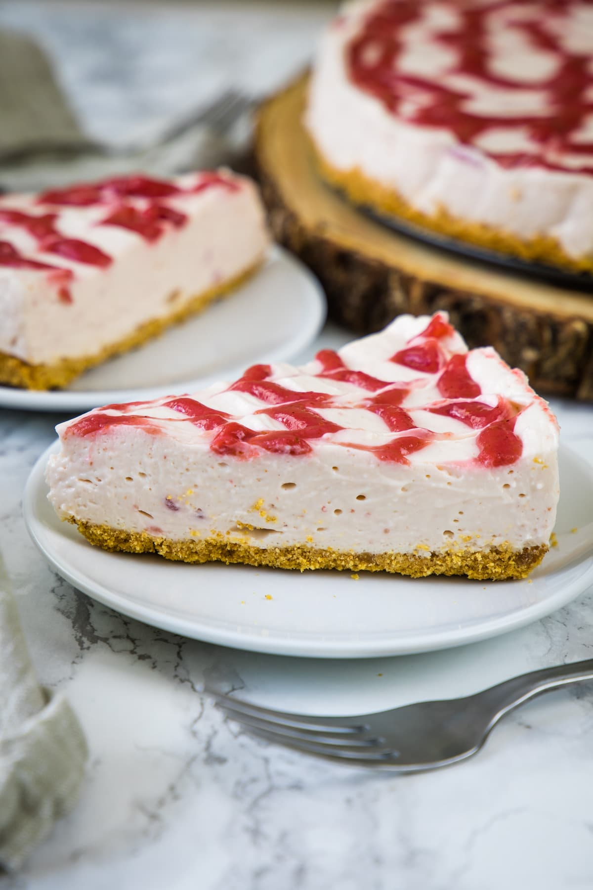 A close up of no bake strawberry cheesecake slice served on a plate with fork on side.