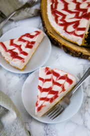 2 sliced of strawberry cheesecake served in plate and remaining on back side.