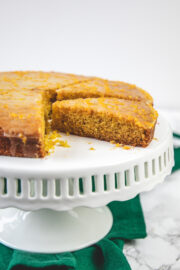 Orange cake on the cake stand with green napkin on side.