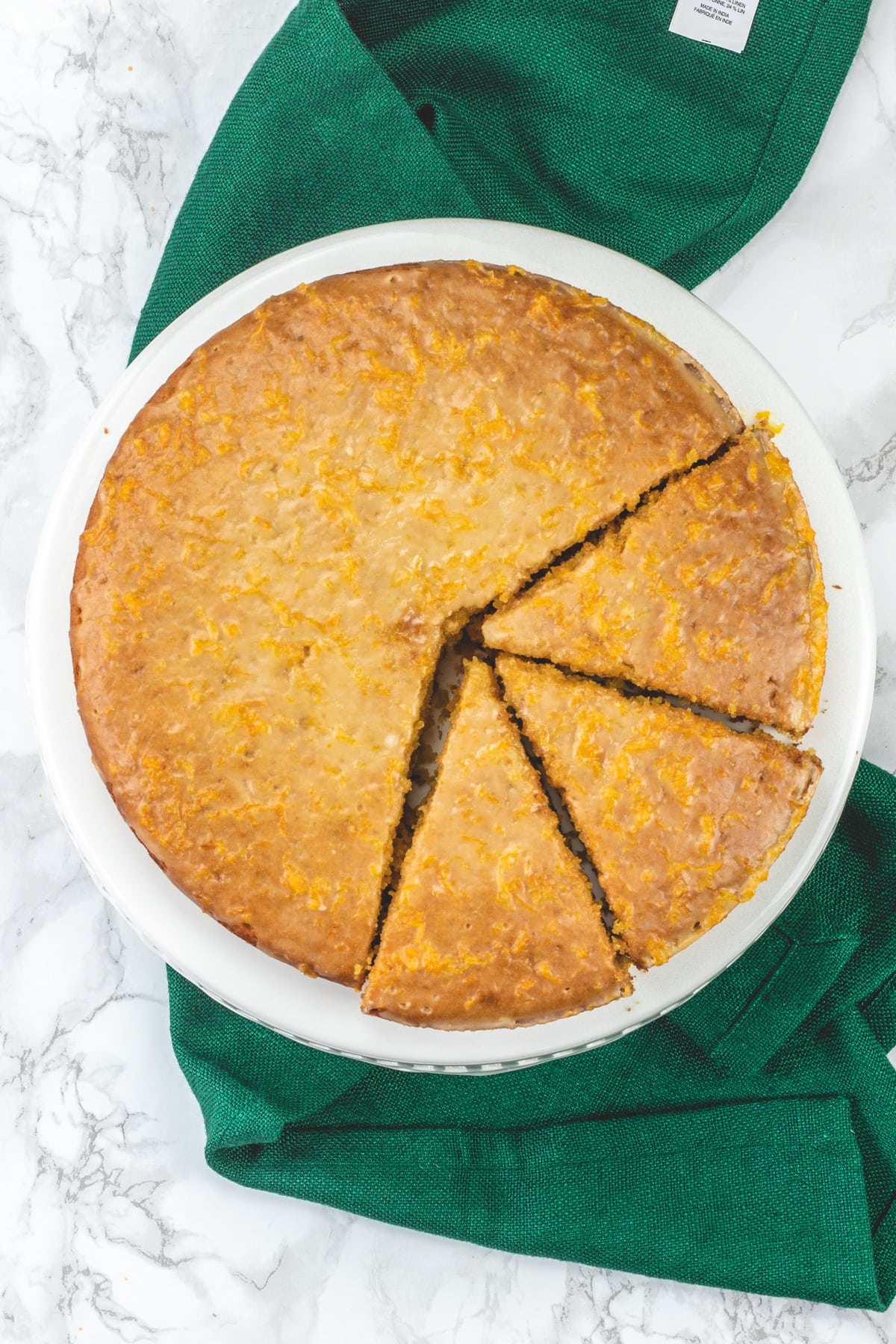 Top view of eggless orange cake on the cake stand with green napkin.