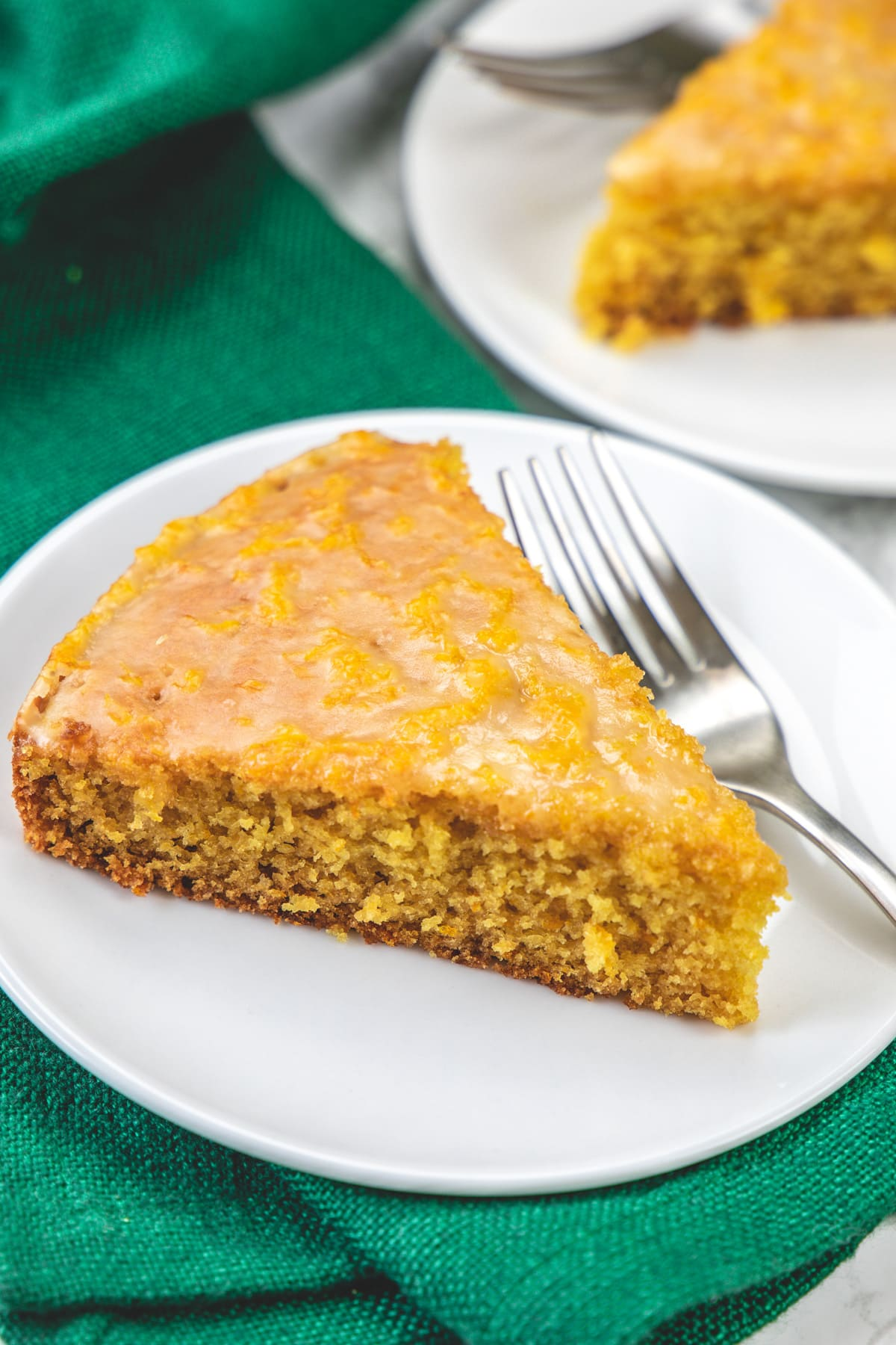 A slice of orange cake in a plate with fork.