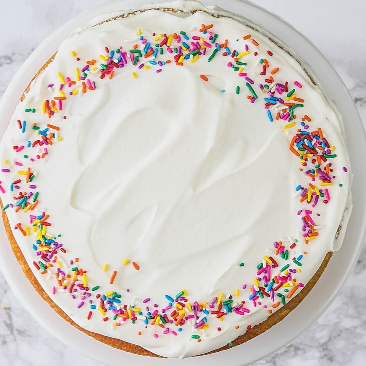 Top view of eggless vanilla cake frosted and decorated with sprinkles.