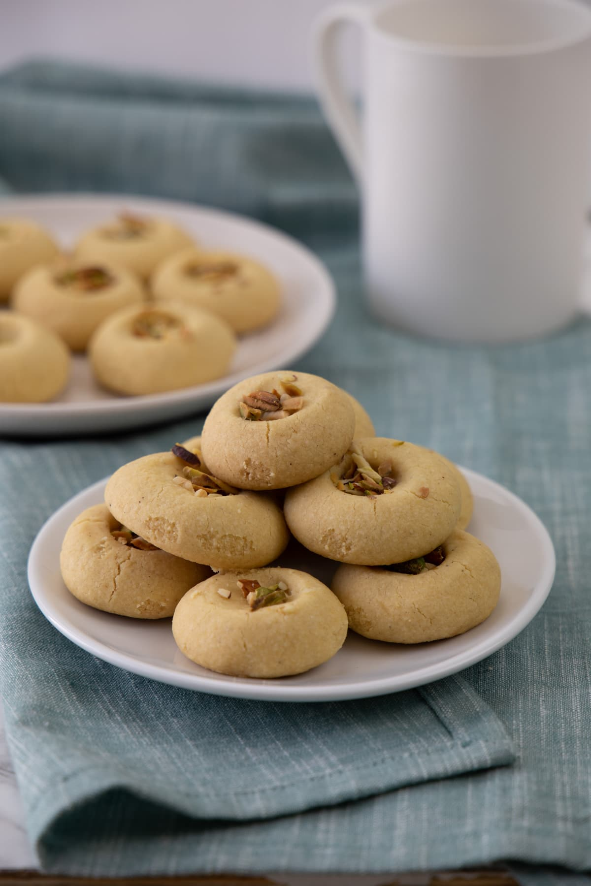 A stack of nankhatai cookies in a plate, few more in background with a cup of coffee.