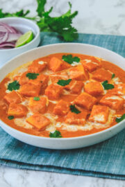 Paneer makhani garnished with cilantro, napkin under the bowl, onion, lime wedge and cilantro in the back.