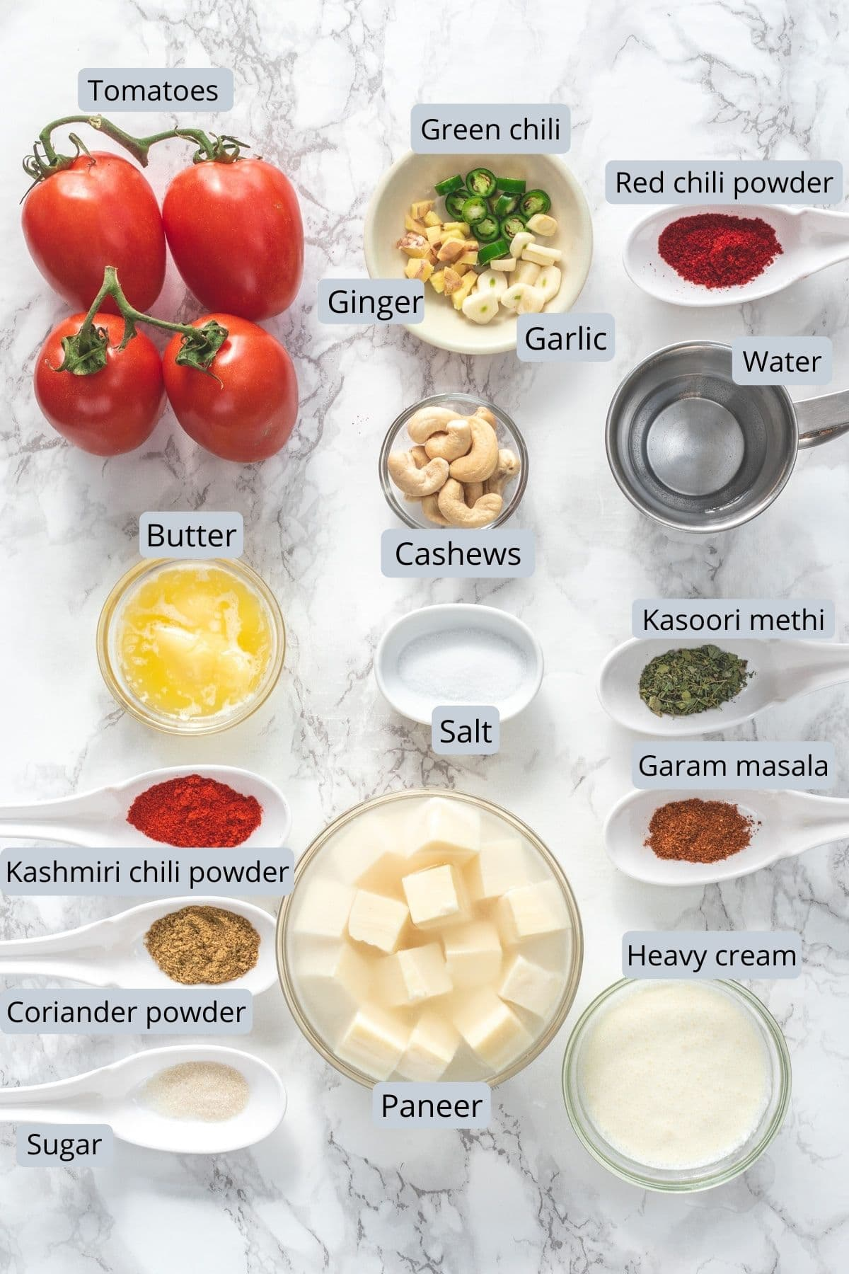 Ingredients used in paneer makhani recipe in individual bowls and spoons.